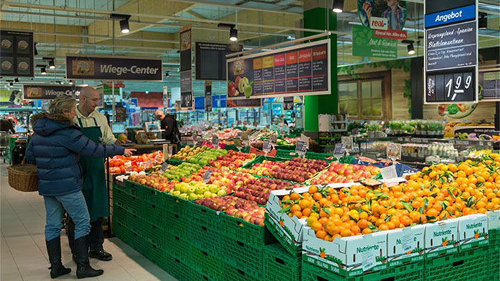 Customers look at fruits at Real which are illuminated using Philips supermarket lighting