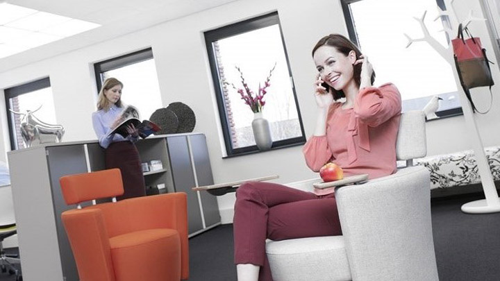 Woman on the phone under Soundlight Comfort solution. Ideal office lighting for more comfortable workplaces.